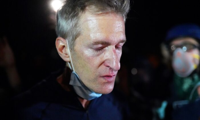 Portland Mayor Ted Wheeler reacts after being exposed to tear gas fired by federal officers while attending a violent demonstration in Portland, Ore., on July 22, 2020. (Nathan Howard/Getty Images)