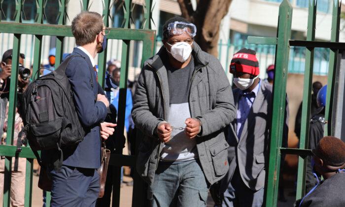 Zimbabwe journalist Hopewell Chin'ono appears at the magistrates courts while handcuffed in Harare, Wednesday, July, 22, 2020. (AP Photo/Tsvangirayi Mukwazhi)