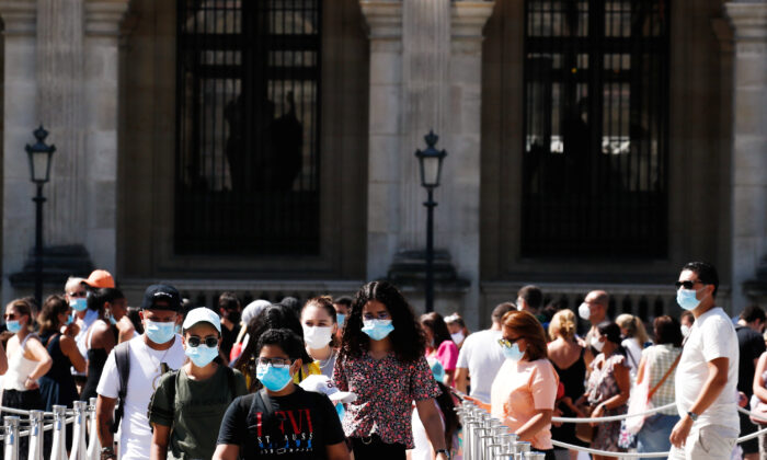 People wearing protective masks walk near the Louvre Museum in Paris on Aug. 6, 2020. (Gonzalo Fuentes/Reuters)