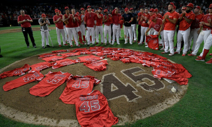 Los Angeles Angels public relations employee Eric Kay (L) joins the Angels players as they lay their jerseys on the pitcher's mound in honor of fallen teammate Tyler Skaggs after they won a combined no-hitter against the Seattle Mariners at Angel Stadium in Anaheim, Calif., on July 12, 2019. (John McCoy/Getty Images)
