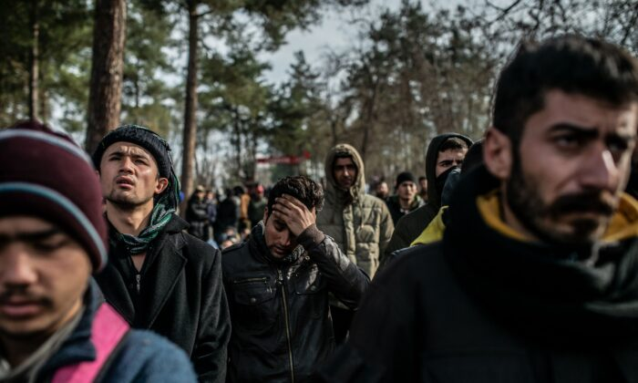 Migrants wait in the buffer zone near the Pazarkule crossing gate in Edirne at the Turkey-Greece border on March 5, 2020. (Bulent Kilic/AFP via Getty Images)