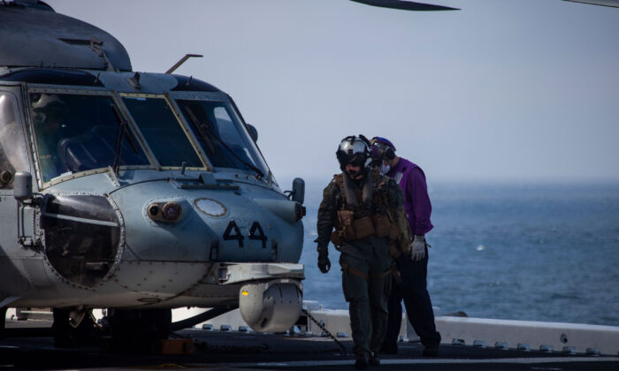 A U.S. Navy MH-60 Seahawk pilot returns to the amphibious assault ship USS Makin Island (LHD-8) during ongoing search and rescue operations following an AAV-P7/A1 assault amphibious vehicle mishap off the coast of Southern California, July 30. (Cpl. Patrick Crosley/Digital/Marine Corps)