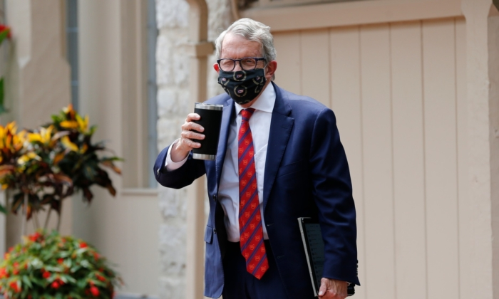 Ohio Gov. Mike DeWine acknowledges members of the media while entering his residence after testing positive for COVID-19 earlier in the day Thurs., Aug. 6, 2020, in Bexley, Ohio. DeWine tested negative later in the day using a more sensitive laboratory-developed test. (Jay LaPrete/AP photo)
