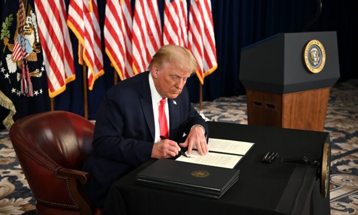 President Donald Trump signs executive orders extending CCP virus economic relief, during a news conference in Bedminster, N.J., on Aug. 8, 2020. (Jim Watson/AFP via Getty Images)