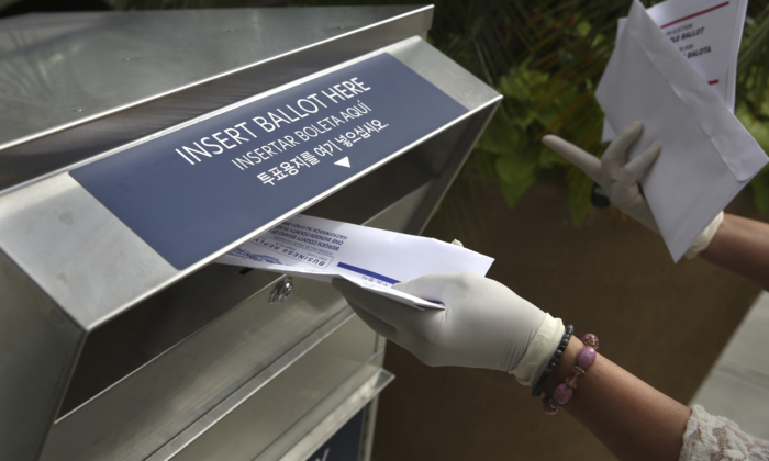 A woman wearing gloves drops off a mail-in ballot at a drop box in Hackensack, N.J., on July 7, 2020. (Seth Wenig/AP Photo)