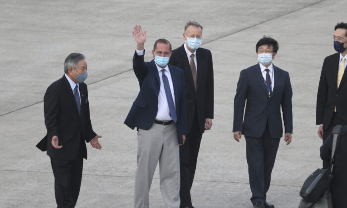 U.S. Health and Human Services Secretary Alex Azar, second left, waves to media as he arrives at Taipei Songshan Airport in Taipei, Taiwan, Sunday, Aug. 9, 2020. (AP Photo/Chiang Ying-ying)