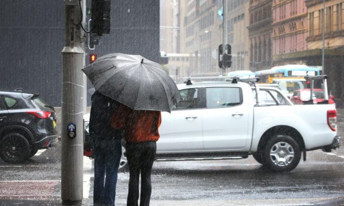 A couple brave heavy rain along Park Street in Sydney, Australia on Feb. 8, 2020. (Lisa Maree Williams/Getty Images)