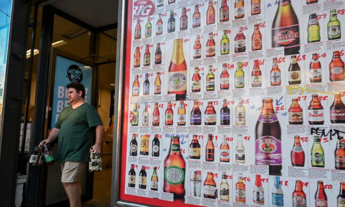 """A man leaves a """"bottle shop"""" displaying a sign showing dozens of beers for sale, in Melbourne, Australia on March 31, 2020. (William West/AFP via Getty Images)"""