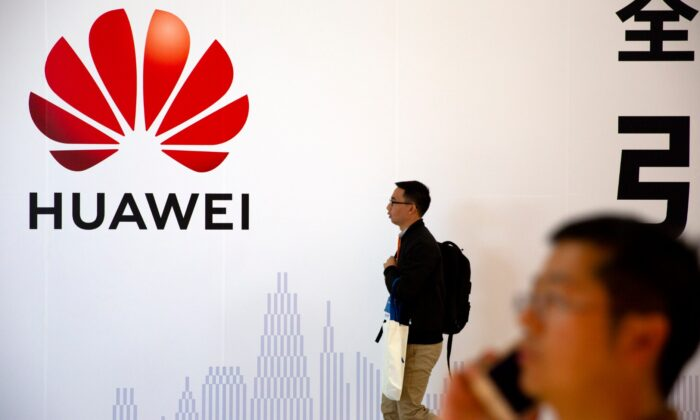 Man uses his smartphone as he stands near a billboard for Chinese technology firm Huawei at the PT Expo in Beijing on Oct. 31, 2019. (Mark Schiefelbein/AP Photo)