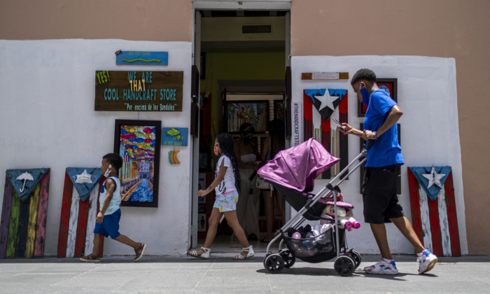 Children walk down a street in Old San Juan, Puerto Rico, on July 20, 2020. (Ricardo Arduengo/AFP via Getty Images)