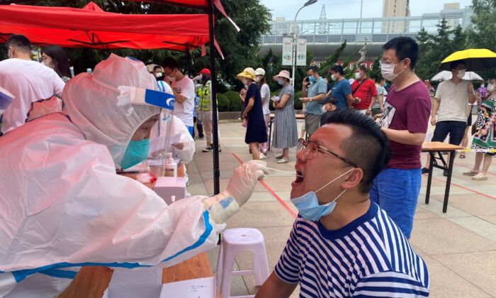 A health worker is carrying out a COVID-19 test in Dalian, in China's northeast Liaoning Province on July 26, 2020. (STR/AFP via Getty Images)