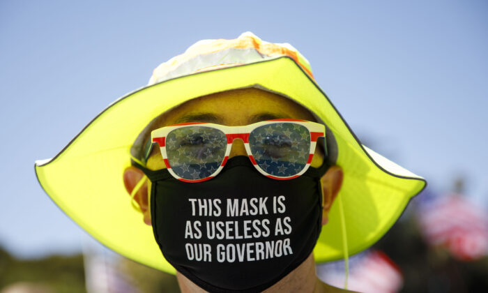A demonstrator wears a facemask referring to the governor of California in Beverly Hills, Calif., on Aug. 8, 2020. (Patrick T. Fallon/AFP via Getty Images)