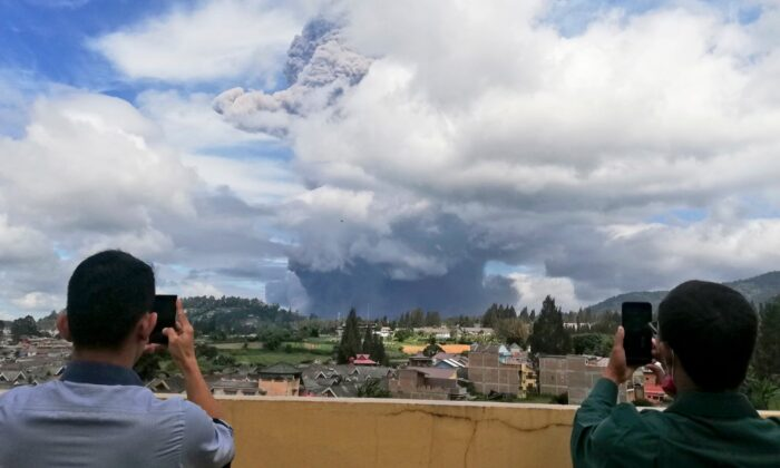Indonesian men use their mobile phones to take photos as Mount Sinabung spews volcanic materials into the air as it erupts, in Karo, North Sumatra, Indonesia, on Aug. 10, 2020. (Sugeng Nuryono/AP Photo)