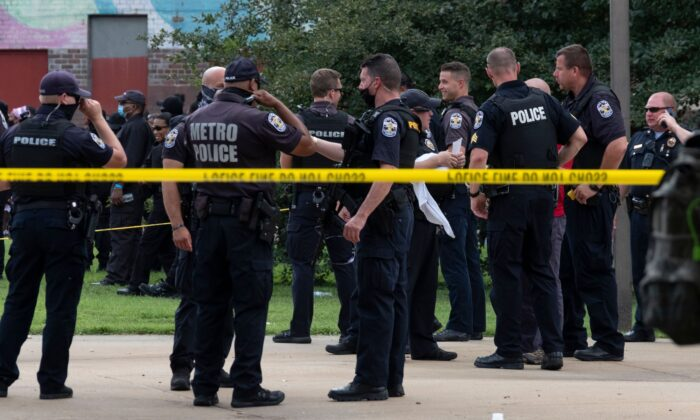 Members of the Louisville Metro Police Department congregate around the place where Breonna Taylor was shot during a rally to protest her killing, in Louisville, Kentucky on July 25, 2020. (Jeff Dean/AFP via Getty Images)