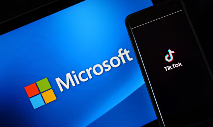 In this photo illustration, a mobile phone featuring the TikTok app is displayed next to the Microsoft logo on Aug. 3, 2020 in New York City. (Cindy Ord/Getty Images)