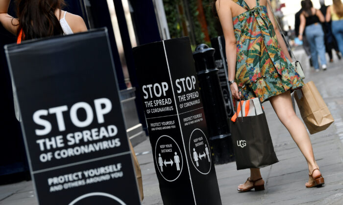 Shoppers walk past social distancing signs at the Covent Garden shopping and dining district, amid the spread of the coronavirus disease (COVID-19), in London on Aug. 2, 2020. (Toby Melville/Reuters)