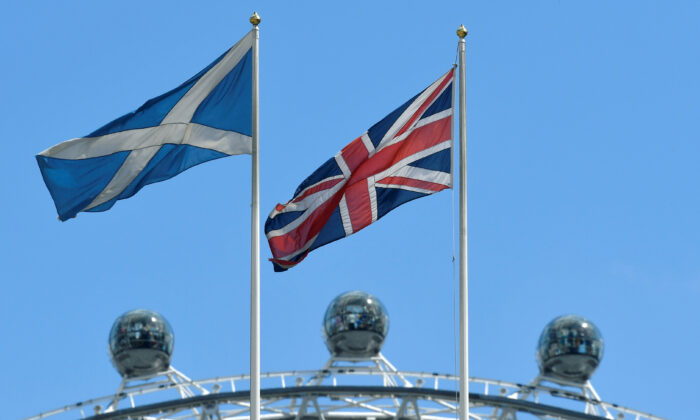 The Scottish Saltire flag flies next to the British Union Jack flag with the London Eye wheel seen behind in London on July 29, 2019. (Toby Melville/Reuters)