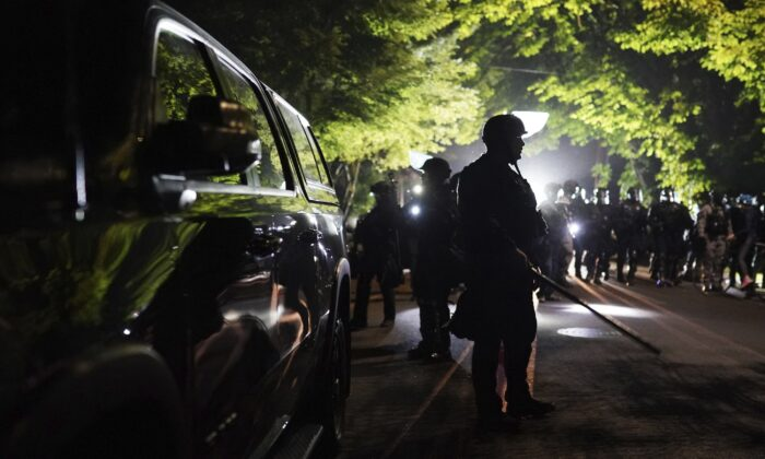 Portland police officers walk through the Laurelhurst neighborhood after dispersing rioters from the Multnomah County Sheriff's Office in Portland, Ore., early Aug. 8, 2020. (Nathan Howard/AP Photo)