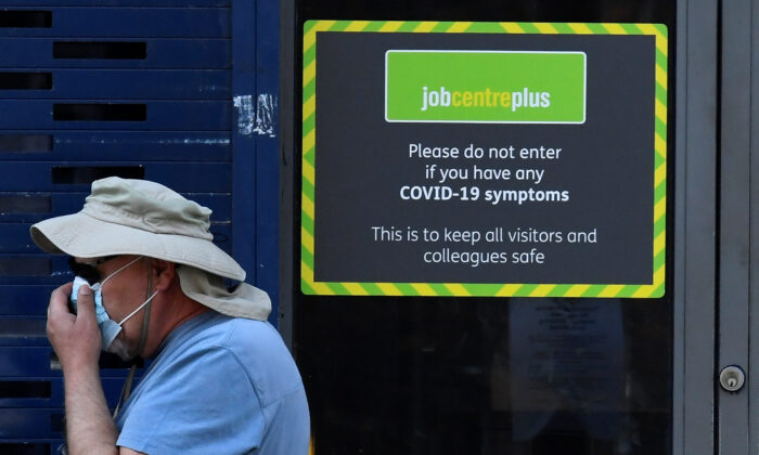 A person wearing a protective face mask walks past a Job Centre Plus office amid the outbreak of the CCP virus in London on Aug. 11, 2020. (Toby Melville/Reuters)