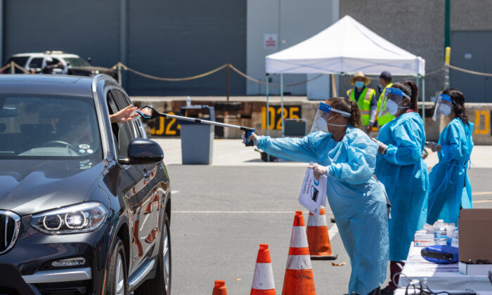 Nurses collect swab tests for COVID-19 at a new, large-scale testing site at the Anaheim Convention Center in Anaheim, Calif., on July 15, 2020. (John Fredricks/The Epoch Times)