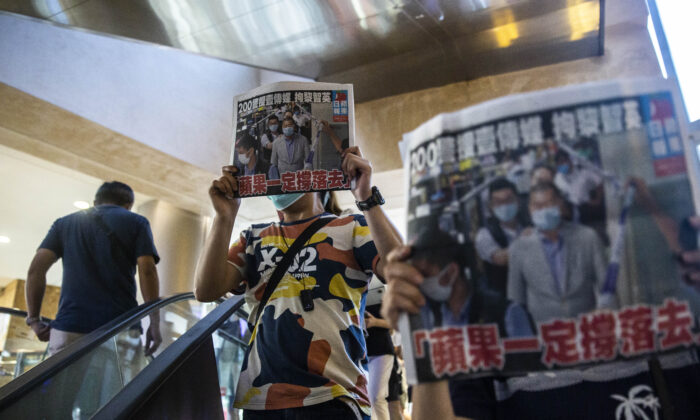 People hold up copies of the Apple Daily as they protest for press freedom inside a mall in Hong Kong on Aug. 11, 2020. (ISAAC LAWRENCE/AFP via Getty Images)