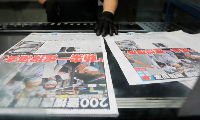 "An employee checks the print quality of copies of the Apple Daily newspaper,  with a headline ""Apple Daily will fight on"" after media mogul Jimmy Lai Chee-ying was arrested by the national security unit, at the company's printing facility in Hong Kong on Aug. 11, 2020. (Tyrone Siu/Reuters)"