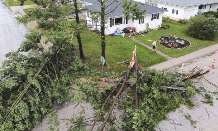 Downed trees and a utility pole in front of the home of Tim and Patricia Terres in Walcott, Iowa, after high winds and heavy rain passed through the area in Davenport, Iowa, on Aug. 10, 2020. (Kevin E. Schmidt/Quad City Times via AP)