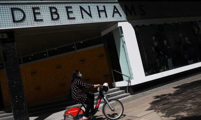 A cyclist wearing a mask goes past Debenhams in Oxford Circus, London, on May 28, 2020. (Hannah McKay/ Reuters)