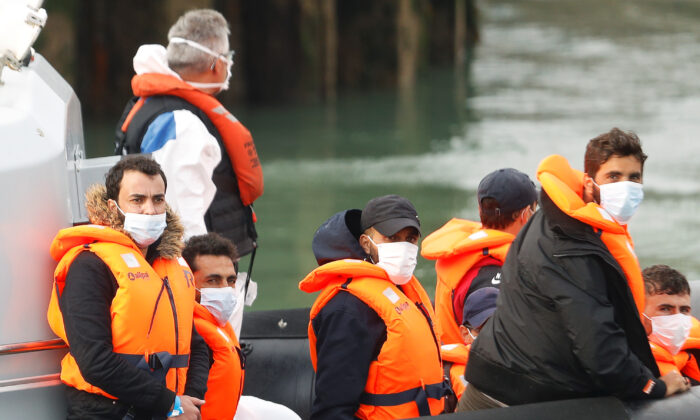 Migrants react as they are brought to Dover harbour by Border Patrol, in Dover, Britain, on Aug. 11, 2020. (Reuters/Peter Nicholls)