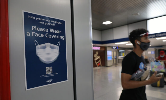People walk through Pennsylvania Station as city workers attempt to hand out information sheets to travelers arriving by train from states affected by rules requiring 14-day quarantines, in New York City on Aug. 6, 2020. (Spencer Platt/Getty Images)
