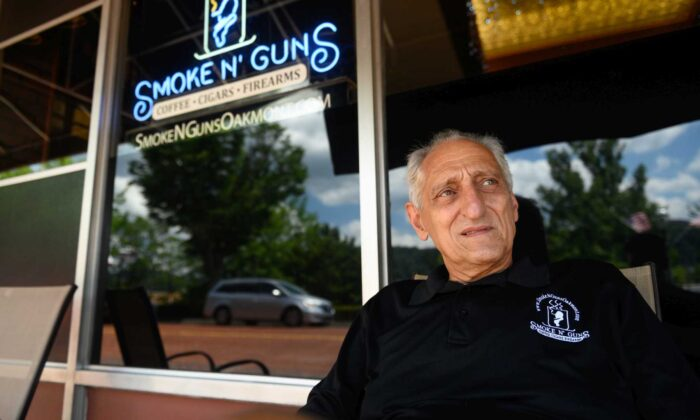 Gregory Ionadi, 75, sits in front of Smoke N' Guns, which he owns with his son, Gregory 'Gooch' Ionadi. (Justin Merriman)