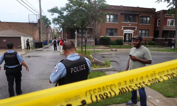 Police secure the scene of a shooting in the Auburn Gresham neighborhood in Chicago, Ill., on July 21, 2020. At least 14 people were transported to area hospitals after several gunmen opened fire on mourners standing outside of a funeral home. More than 2000 people have been shot and more than 400 have been murdered in Chicago so far this year. (Scott Olson/Getty Images)
