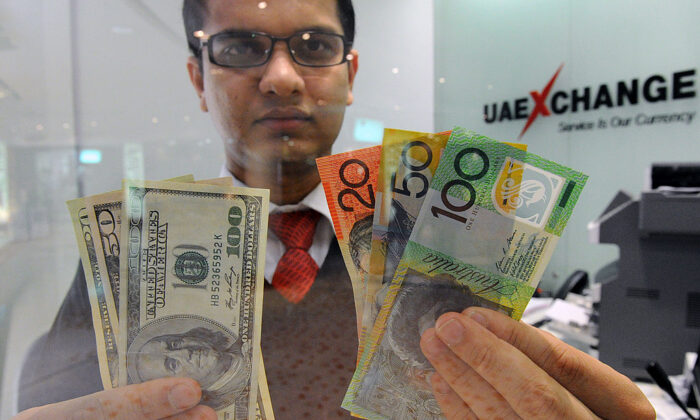 Money changer Tirth Acharya of India displays a selection of US dollars (L) and Australian polymer notes (R) as the local currency reached parity in Sydney on May 14, 2012. (TORSTEN BLACKWOOD/GettyImages)