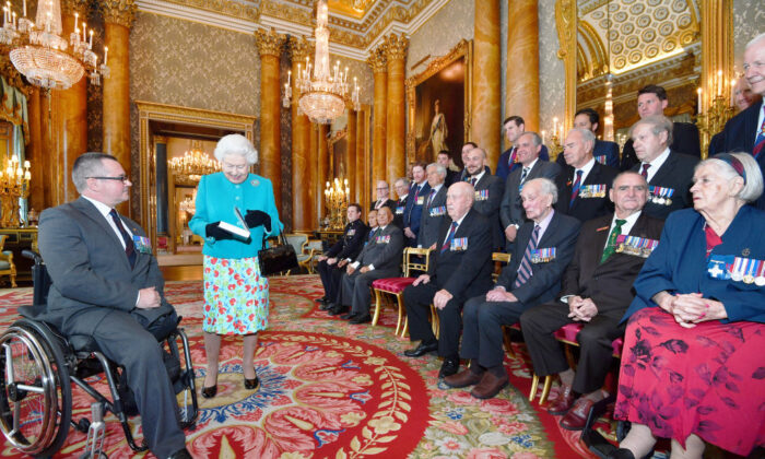 Queen Elizabeth II is given a book by Major Peter Norton GC, which recalls the exploits by the twenty-five living recipients of the Victoria and George Cross medals, during a reception for the Victoria Cross and George Cross Association at in the Picture Gallery at Buckingham Palace on May 16, 2018 in London, England. (John Stillwell - Pool/Getty Images)