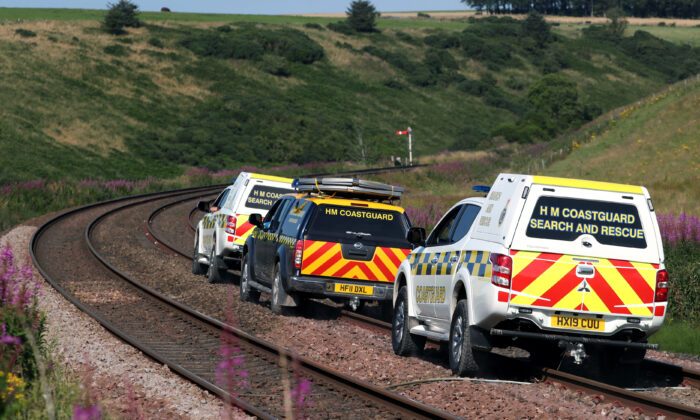 Emergency service vehicles ride along the tracks near the scene of a derailed passenger train, near Carmont, Stonehaven, Scotland, Britain, on Aug. 12, 2020. (Russell Cheyne/Reuters)