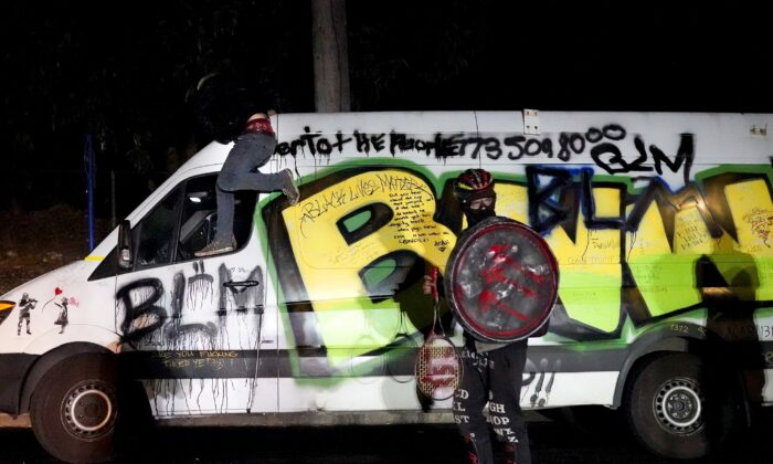 A man carrying a shield with a symbol linked to Antifa stands next to a van with Black Lives Matter imagery during a demonstration outside a Multnomah County sheriff's office building in north Portland, Ore., on Aug. 12, 2020. (Nathan Howard/Getty Images)