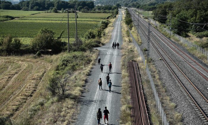 Migrants walk along rail tracks near Idomeni at the border between Greece and North Macedonia, on July 16, 2020. (Sakis Mitrolidis/AFP via Getty Images)
