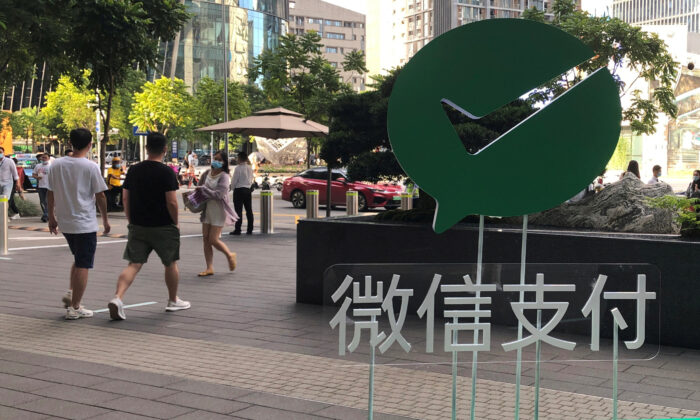 People walk past a Wechat Pay sign at the Tencent company headquarters in Shenzhen, Guangdong province, China on Aug. 7, 2020. (Reuters/David Kirton)