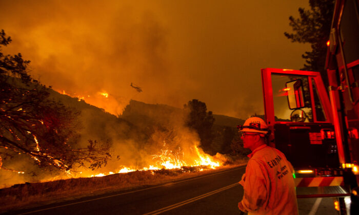 A firefighter watches as a helicopter drops water on the Lake Hughes fire in Angeles National Forest, north of Santa Clarita, Calif., on Aug. 12, 2020. (Ringo H.W. Chiu/AP Photo)