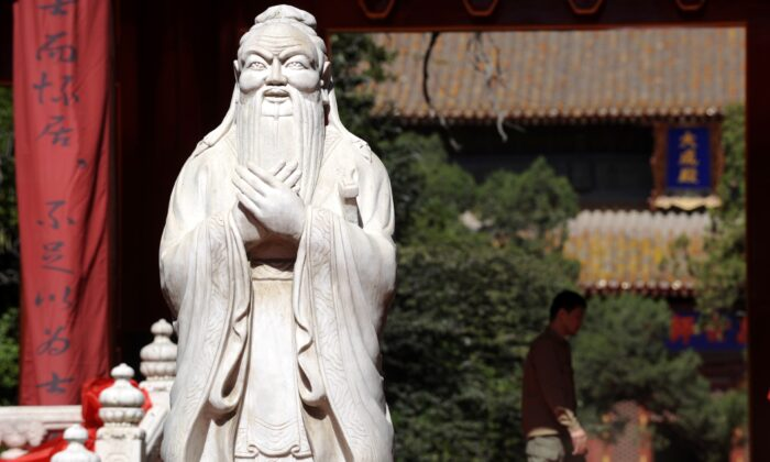 A man walks behind a statue of Confucius at the Confucius Temple in Beijing on September 28, 2010. (LIU JIN/AFP via Getty Images)