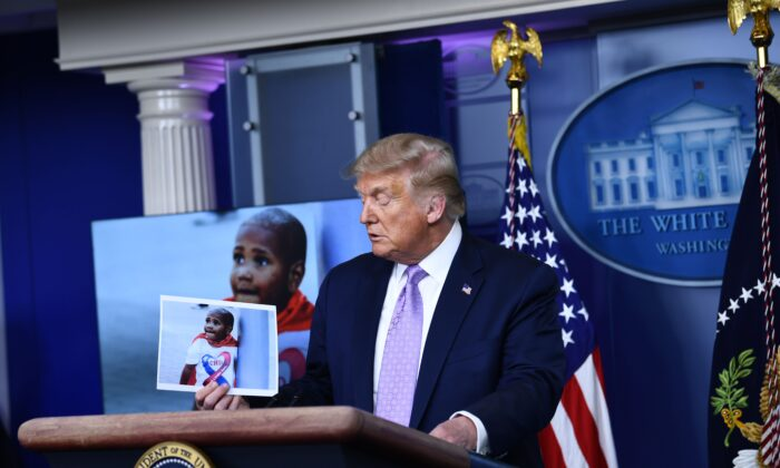President Donald Trump holds up a photo of LeGend Taliferro, a victim of a crime during a news conference in the Brady Briefing Room of the White House in Washington, on Aug. 13, 2020. (Brendan Smialowski / AFP / Getty Images)