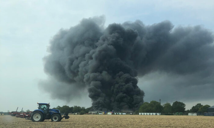 Smoke can be seen after a fire broke out at an industrial unit at Parham Airfield, in Suffolk, England, on Aug. 13, 2020.(Courtesy of Richard Lapage)