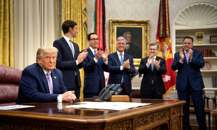 (L-R, rear) Senior Advisor Jared Kushner, Secretary of the Treasury Steven Mnuchin, National Security Advisor Robert O'Brien and others clap for President Donald Trump (L) after he announced an agreement between the United Arab Emirates and Israel to normalize diplomatic ties, the White House on Aug. 13, 2020. (Brendan Smialowski/AFP via Getty Images)