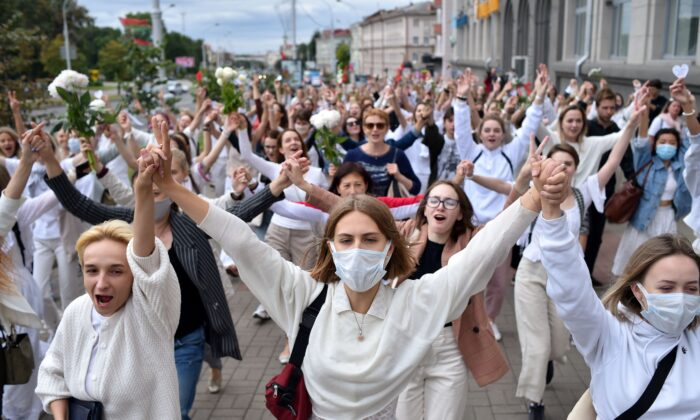 Women dressed in white clothes protest against police violence during recent rallies of opposition supporters, who accuse strongman Alexander Lukashenko of falsifying the polls in the presidential election, in Minsk on Aug. 12, 2020. (Sergei Gapon/AFP via Getty Images)