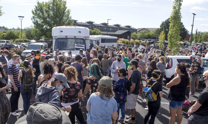 Hundreds of activists gather around two  buses outside the Crane Shed Commons in Bend, Ore., on Aug. 12, 2020. (Ryan Brennecke/The Bulletin via AP)