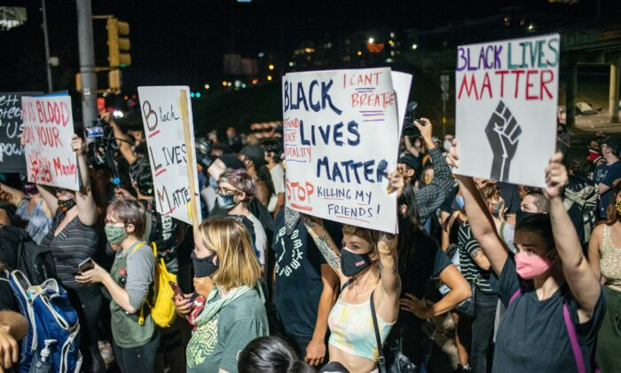 People hold up signs outside Austin Police Department after a vigil for Garrett Foster, a Black Lives Matter protester who was shot dead after allegedly brandishing his firearm at a driver, in Austin, Texas, on July 26, 2020. (Sergio Flores/Getty Images)