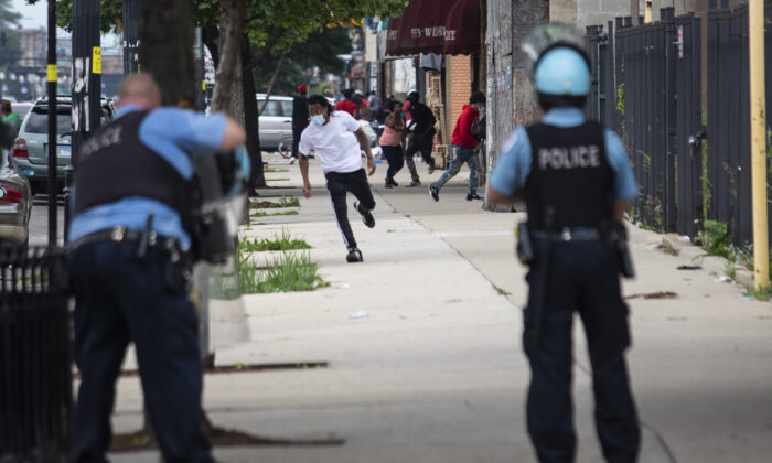 Chicago police officers respond to shots fired near reports of rioting on West Madison Street near South Karlov Avenue on the West Side, of Chicago, Aug. 10, 2020. (Ashlee Rezin Garcia/Chicago Sun-Times via AP)