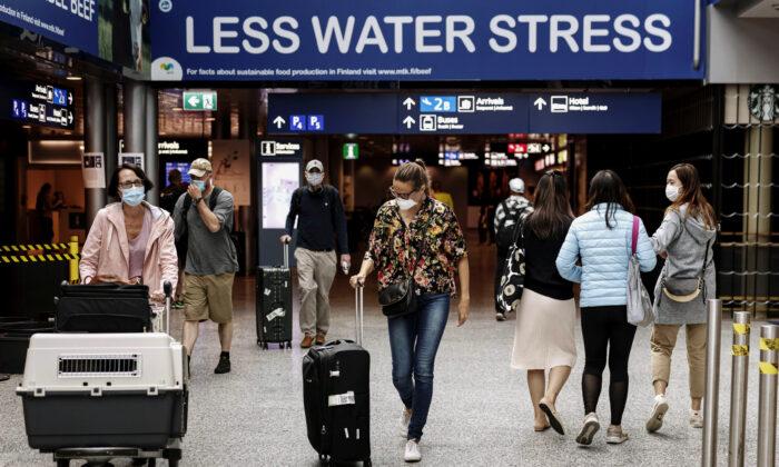 Passengers wear masks as they walk at the Helsinki-Vantaa airport in Vantaa, Finland, on July 13, 2020. (Roni Rekomaa/Lehtikuva/Reuters)