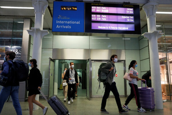 Passengers wearing protective face masks arrive from Paris at Eurostar terminal at St Pancras station, as Britain imposes a 14-day quarantine on arrival from France
