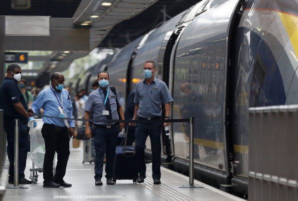 Passengers and staff wearing protective face masks arrive from Paris at Eurostar terminal at St Pancras station, as Britain imposes a 14-day quarantine on arrival from France